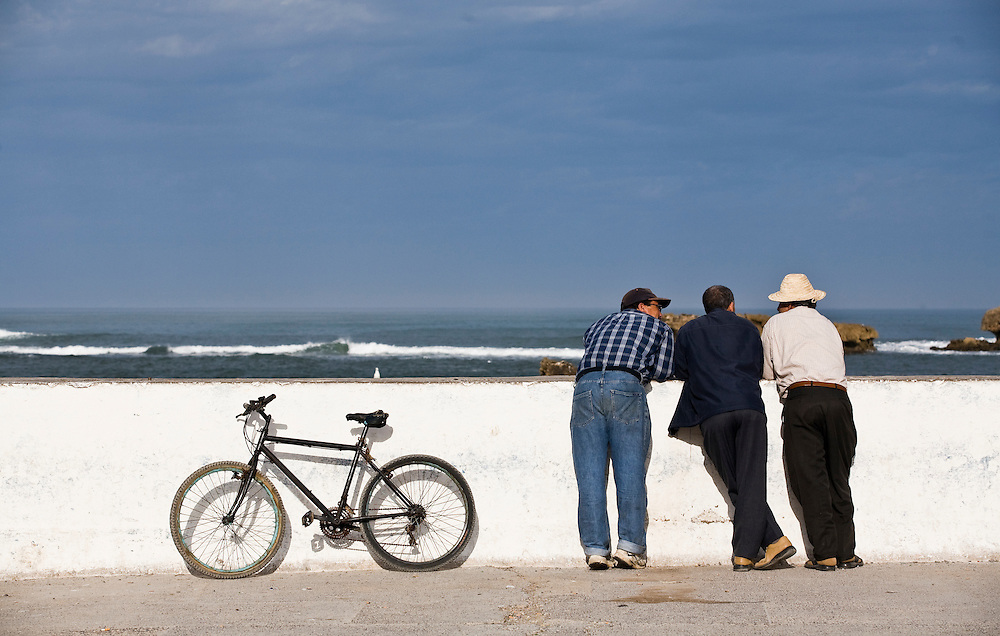 Three men relax and talk in the morning on the sea wall around the town of Essaouira, Morocco