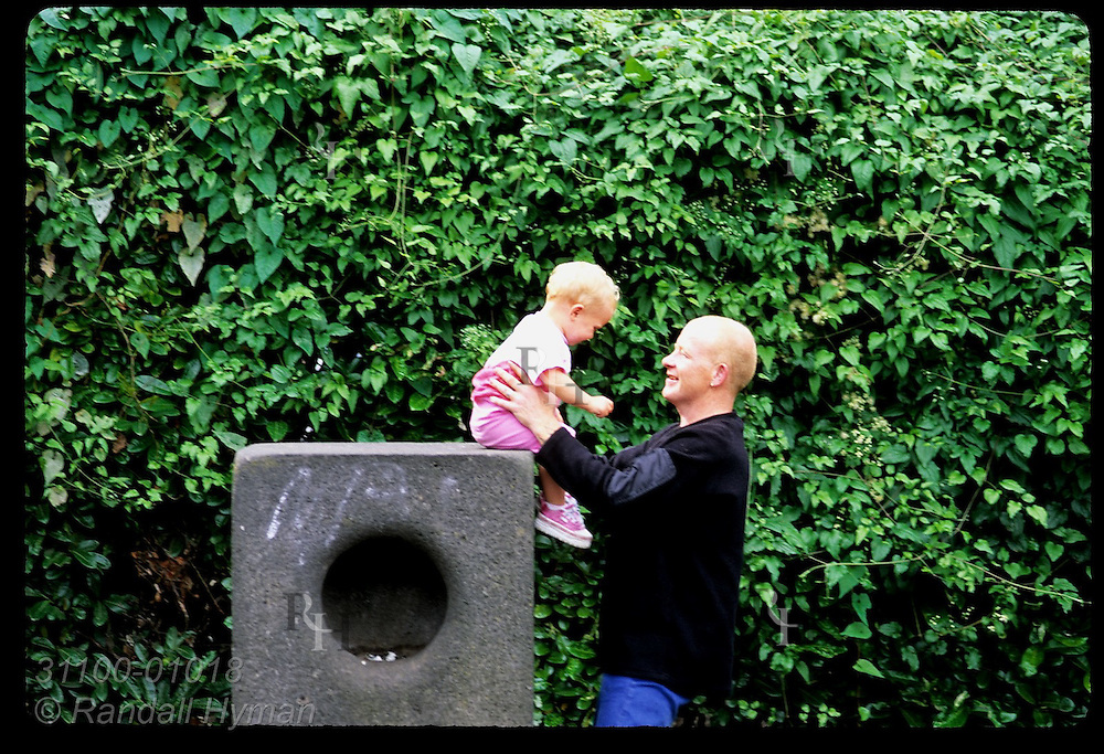 Laughing dad helps toddler daughter off concrete pedestal at St. Stephen's Green; Dublin, Ireland.