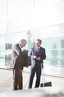 Businessmen standing while talking in the airport