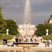 Arc de Triomphe du Carrousel and fountain at Jardin des Tuileries sculpture garden with the Musee du Louvre in back, Paris France<br />