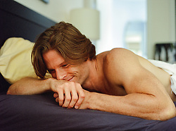 sexy man in bed smiling to himself
