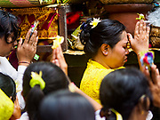 "02 AUGUST 2017 - UBUD, BALI, INDONESIA: Market venders pray in the temple during the ""Merchants' Day"" ceremony at the Pura (Temple) Melanting Pasar Ubud, the small Hindu temple in the Ubud market. It's a day that merchants throughout Ubud come to the temple to make offerings and pray for prosperity.    PHOTO BY JACK KURTZ"