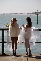 © Licensed to London News Pictures. 02/10/2015. Southsea, Hampshire, UK. Two women having a photoshoot dressed in wedding attire in the sunny weather at the 'hot walls' in Old Portsmouth, Hampshire today, 2nd October 2015. The weekend weather is set to be dry and fine day in the south of England. Photo credit : Rob Arnold/LNP
