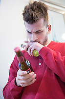 Young man reading label on beer bottle in cafe