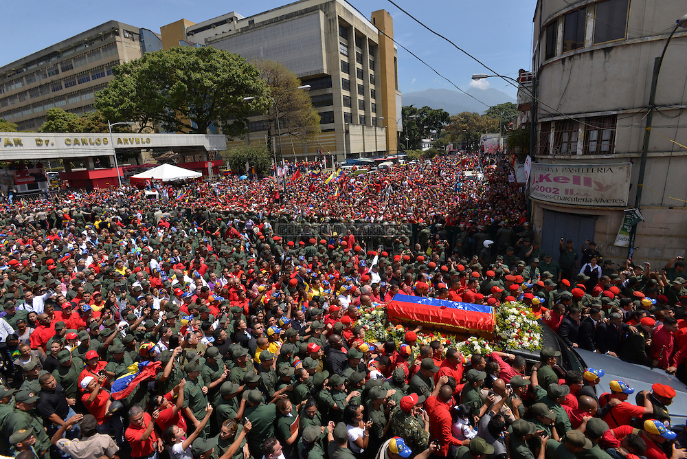 CARACAS - MARCH 06, 2012: Supporters of President Hugo Chávez accompany his funeral procession to the military academy, where he will remain and may be visited publicly. Chavez was treated for cancer two years in Cuba and returned to Venezuela a few days before his death was officially announced on March 5. (Photo by Gregorio Marrero)