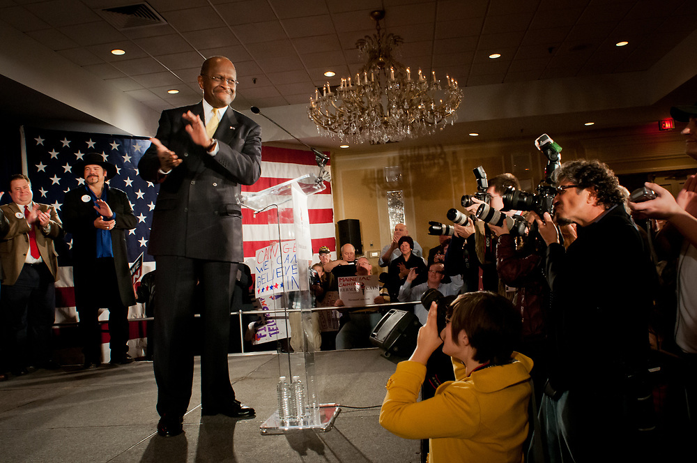 Presidential hopeful Herman Cain takes to the stage during a campaign Rally in the Radisson Hotel in Nashua, NH.