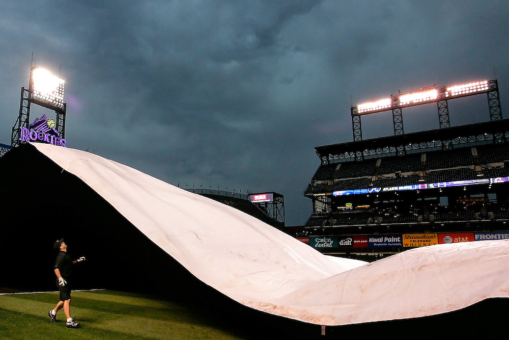 A member of the grounds crew tries to wrangle in the tarp following a rain delay prior to the game between the Atlanta Braves and Colorado Rockies at Coors Field on July 19, 2011 in Denver, Colorado.
