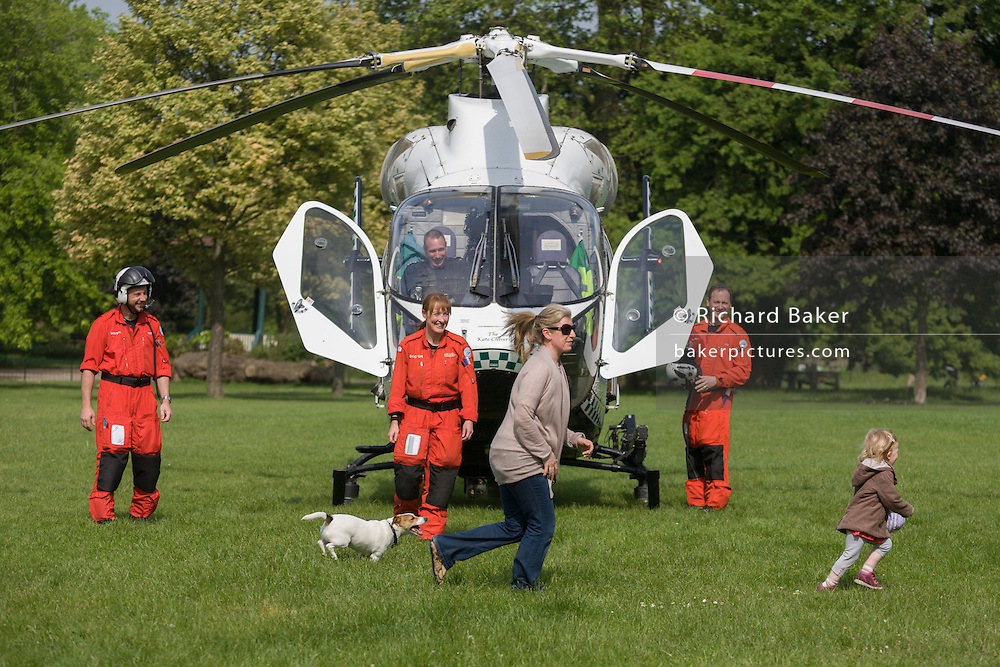 MD902 Explorer helicopter crew from the Kent, Surrey & Sussex Air Ambulance Trust and and mother chasing child on the ground in Ruskin Park after emergency flight to Kings College Hospital in south London.