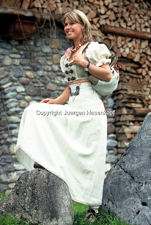 Sport,Tennis, Anke Huber posiert, modelled in einem Dirndl,Tracht,privat,stehend,laechelnd,ganze Figur,.Hintergrund rustikale Steinmauer und Holzstoss, Going 06.04.1997,