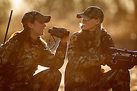 DEER HUNTERS TAKING A BREAK TO CHAT WHILE HUNTING HOLDING BINOCULARS AND A RIFLE