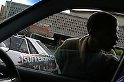 A man is selling newspapers at a junction in central Cape Town.