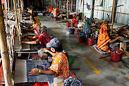 (Facing left, top-bottom) Murunnahar Khatun (blue hat), Mosiammat Rahimah Begum (yellow sari), Mosammat Reshona Khatun (red sari) and Mosammat Dulali Begum (grey hat) work on their rugs at the Mornia Kik Rug Factory in Doani Villlage, Haragach Upazila, Rangpur, Bangladesh on 19th September 2011 where they work alongside 25 rural village women making rugs for German textile discounter Kik. Over 400 women have been economically empowered through the CARE Bangladesh WONDER Project that was completed recently. The WONDER Project's goals were to create sustainable income and employment opportunities for extremely poor women by training them in rug production for export. The women now earn about 4000 Bangladeshi Taka per month. The WONDER Project has now moved into a new phase that focusses on general healthcare, workplace safety and nutritional training and awareness programs. Photo by Suzanne Lee for The Guardian