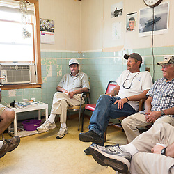 August 4, 2017 - Tangier Island, VA - <br /> Inside the &quot;Situation Room,&quot;  (named after a small briefing room in the White House) is a small room inside the former Tangier Island health clinic, where watermen gather at the end of the day to &quot;solve all the world's problems,&quot; according to Tangier Island Mayor James &quot;Ooker&quot; Eskridge (center).  From left to right, George Cannon, Richard Pruitt, Mayor Eskridge, and Danny McCready, right, discuss the day's latest.  Photo by Susana Raab/Institute