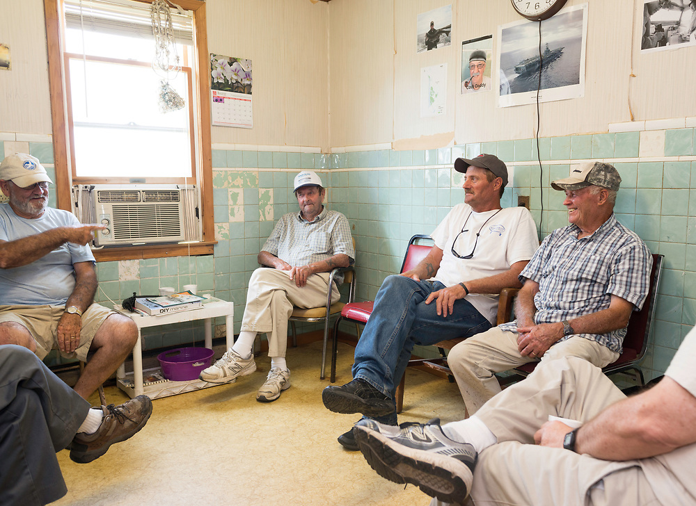"""August 4, 2017 - Tangier Island, VA - <br /> Inside the """"Situation Room,""""  (named after a small briefing room in the White House) is a small room inside the former Tangier Island health clinic, where watermen gather at the end of the day to """"solve all the world's problems,"""" according to Tangier Island Mayor James """"Ooker"""" Eskridge (center).  From left to right, George Cannon, Richard Pruitt, Mayor Eskridge, and Danny McCready, right, discuss the day's latest.  Photo by Susana Raab/Institute"""