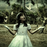 Conceptual image of young girl with long dark hair dressed in white wearing gloves looking amazed at white butterflies
