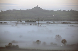 © Licensed to London News Pictures. 25/01/2014. Somerset, UK Glastonbury Tor stand above the mist. Fog on the Somerset Levels near Glastonbury at Sunrise today. Photo credit : Jason Bryant/LNP