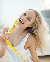 Portrait of woman laughing while holding fork wrapped with measuring tape