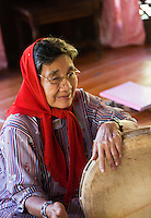 Older woman playing drums for a traditional Malay dance performance at Sarawak Cultural Village.