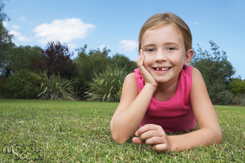 Portrait of girl (5-6) lying in grass leaning on elbow