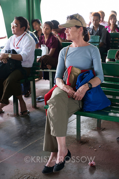 "While in Myanmar, voyagers traveled on the ""Twante Tour"" field program to visit the small town of Twante in the Ayeyawaddy Delta where they visited a local market and pottery workshop before going to a monastic orphanage to make a donation and interact with the children. Portrait of Lifelong Learner Maureen McCartin from Portland, Oregon, while he rides the ferry from Twante."