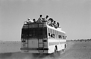 Over crowded bus leaving village in dust