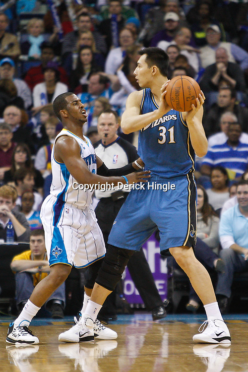 February 1, 2011; New Orleans, LA, USA; Washington Wizards power forward Yi Jianlian (31) is guarded by New Orleans Hornets point guard Chris Paul (3) during the first quarter at the New Orleans Arena.   Mandatory Credit: Derick E. Hingle