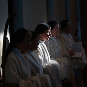 Early morning light streams to Sister Christine Reinhart  meditating during Lauds,  the second of two morning prayer sessions at Our Lady of the Mississippi Abbey  near Dubuque, Iowa.  The community of 22 Roman Catholic women follow Jesus Christ through a life of prayer, silence, simplicity and ordinary work.  Their home is a beautiful monastery which sits high on a bluff, overlooking the Mississippi River.