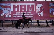 Mongolia. man on horse in front of a big portrait of Lenin/  Pancarte vieillie de propagande communiste.<br />  - Le Parti, c'est l'essence même de l'honnêteté, de l'honneur et de l'intelligence de notre époque! - <br /> Un cavalier de passage pose devant une pancarte tombée en désuétude dans une société en pleine transfomation des mentalités. (Ville de ULIASTAI, capitale de l'aymag de ZAVQAN; le 20 juillet 1992).