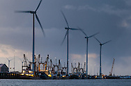 Fishing boats and spinning wind turbines at dusk in Eemshaven, Netherlands