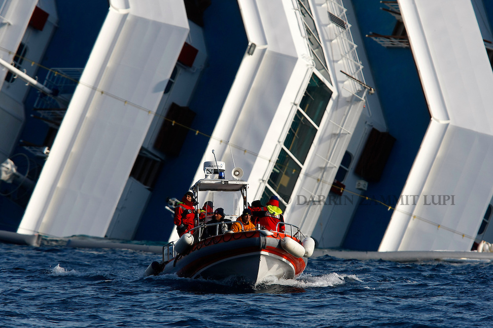 Firefighters in a RHIB (Rigid-hulled inflatable boat) return to harbour from the cruise liner Costa Concordia off the west coast of Italy at Giglio island January 30, 2012. Search operations at the Costa Concordia resumed on Monday after being suspended for a day due to weather conditions and some movement of the capsized cruise ship...REUTERS/Darrin Zammit Lupi (ITALY)