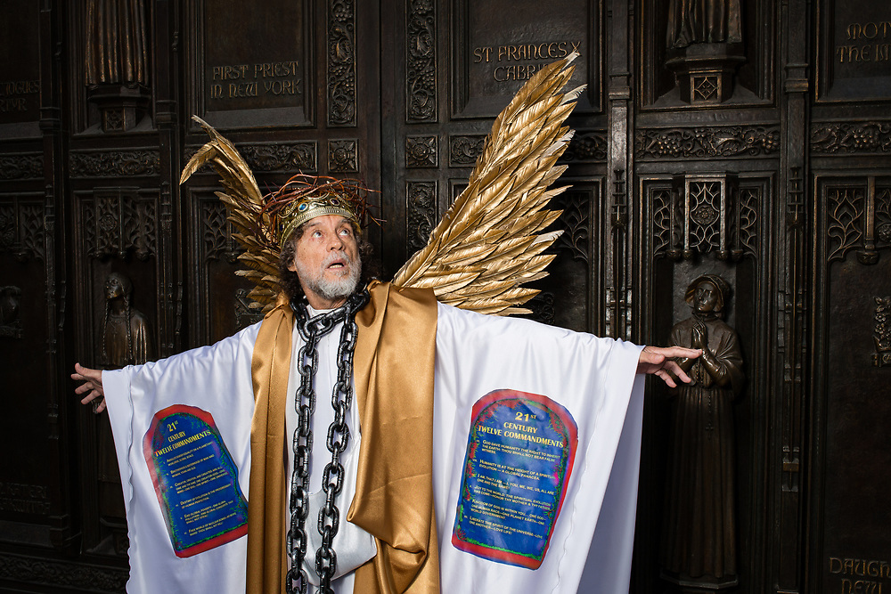 New York, NY - 21 April 2019. A man costumed as an angel with twelve commandments for the 21st Century at the Easter Bonnet Parade and Festival on New York's Fifth Avenue.