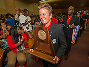 Houston ISD Athletic Director Marmion Dambrino carries one of two UIL State Basketball Championship trophies into a celebration at Yates High School, September 2, 2014., 2014.
