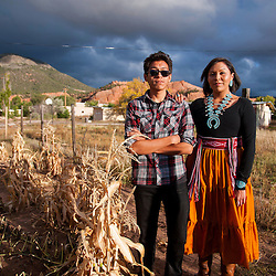 Kayla Begay stands with her brother in their garden  in Navajo, N.M.