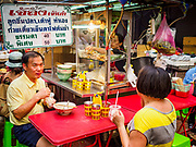 "18 MAY 2017 - BANGKOK, THAILAND: People eating at a street food stall in Bangkok's Chinatown. City officials in Bangkok have taken steps to rein in street food vendors. The steps were originally reported as a ""ban"" on street food, but after an uproar in local and international news outlets, city officials said street food vendors wouldn't be banned but would be regulated, undergo health inspections and be restricted to certain hours on major streets. On Yaowarat Road, in the heart of Bangkok's touristy Chinatown, the city has closed some traffic lanes to facilitate the vendors. But in other parts of the city, the vendors have been moved off of major streets and sidewalks.      PHOTO BY JACK KURTZ"