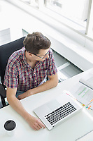 High angle view of businessman working at desk in creative office