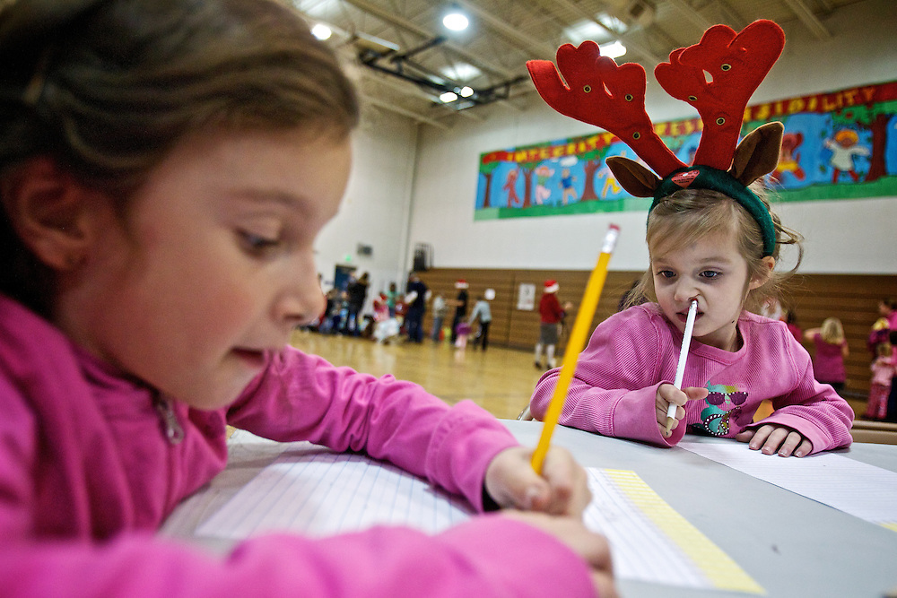 Tori Sims, 5, right, thinks about what she is going to write in her letter to Santa Claus as her sister Hailey, 7, scribes her note at Ponderosa Elementary's Christmas festival Thursday in Post Falls. Students were able to write letters to Santa or soldiers, have their pictures taken with Santa, choose a free book and enjoy Christmas cartoons, cookies and milk during the event sponsored by local businesses and hosted by middle school honor roll students.