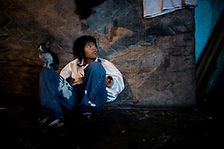 A girl sits on the ground while her boyfriend gets high smoking crack in Mexico City.  Drugs use has been rising in Mexico City.  Low level dealers are now paid more often in drugs instead of money, and increased border security causes more drugs to stay in the country.  In the capital many homeless children and adults are addicted to sniffing paint thinner and also to crack.