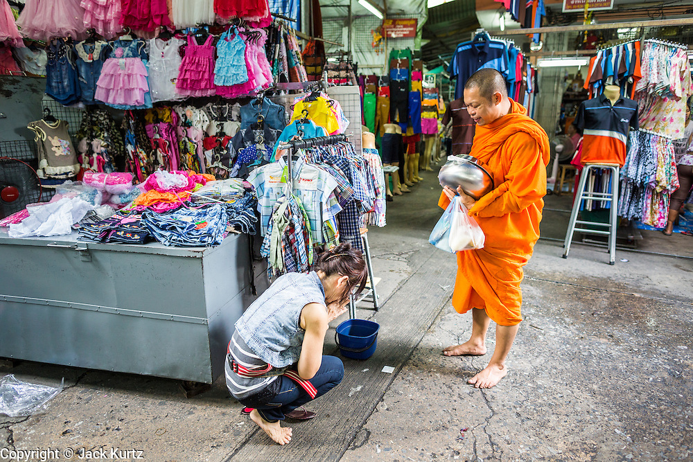06 JUNE 2013 - BANGKOK, THAILAND:     A Buddhist monk blesses a woman who made merit by giving him food his morning alms rounds in Bobae Market in Bangkok. Bobae Market is a 30 year old market famous for fashion wholesale and is now very popular with exporters from around the world. Bobae Tower is next to the market and  advertises itself as having 1,300 stalls under one roof and claims to be the largest garment wholesale center in Thailand.       PHOTO BY JACK KURTZ