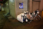 Homeless person's bicycle parked during night time inside a shopping mall in Kamagasaki.