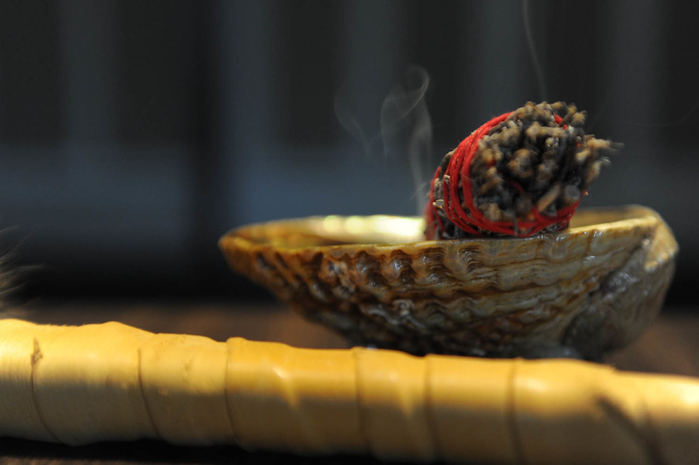 """Haudenosaunee-Seneca Holy Woman, Shianne Eagleheart, burns sage to cleanse and protect the space where the healing circle meets..""""In our indigenous communities, our good medicine way is to respond to our Veterans when they are deployed or return from combat.  We attend to their heart and soul needs."""" says Eagleheart.  (Laura Fong Torchia / Special to the Akron Beacon Journal)"""