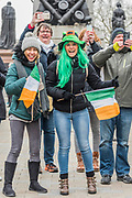People in many types of green hats/headresses are well wrapped up against the cold as they watch the parade go by -  the London St Patrick's Day parade from Piccadilly to Trafalgar Square.