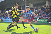 Tom Hopper of Scunthorpe United  crosses ball against Burton Albion defender Tom Flanagan (30)  during the Sky Bet League 1 match between Scunthorpe United and Burton Albion at Glanford Park, Scunthorpe, England on 9 April 2016. Photo by Ian Lyall.
