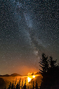 A small spot fire caused by lightning flares up under the Milky Way, in Olympic National Park.