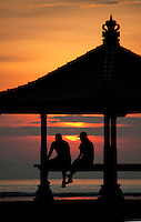 Two figures in a pagoda silhouetted against the rising sun in Bali, Indonesia