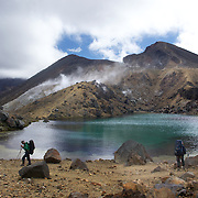 Walkers at the Emerald Lake on the Tangariro Alpine Crossing.  The Tongariro Alpine Crossing is a 7-8 hour hike traversing two active volcanoes within the Tongariro National Park, North Island, New Zealand.  It is considered to be the best one day hike in New Zealand and in the top 10 one day hikes in the world. Packed into the 19.4km hike is an array of diverse landscapes and vegetations. From tussock like alpine meadows, to rugged lava flows, desert like craters and emerald lakes.  The Tongariro Alpine  9th January 2011. Photo Tim Clayton..