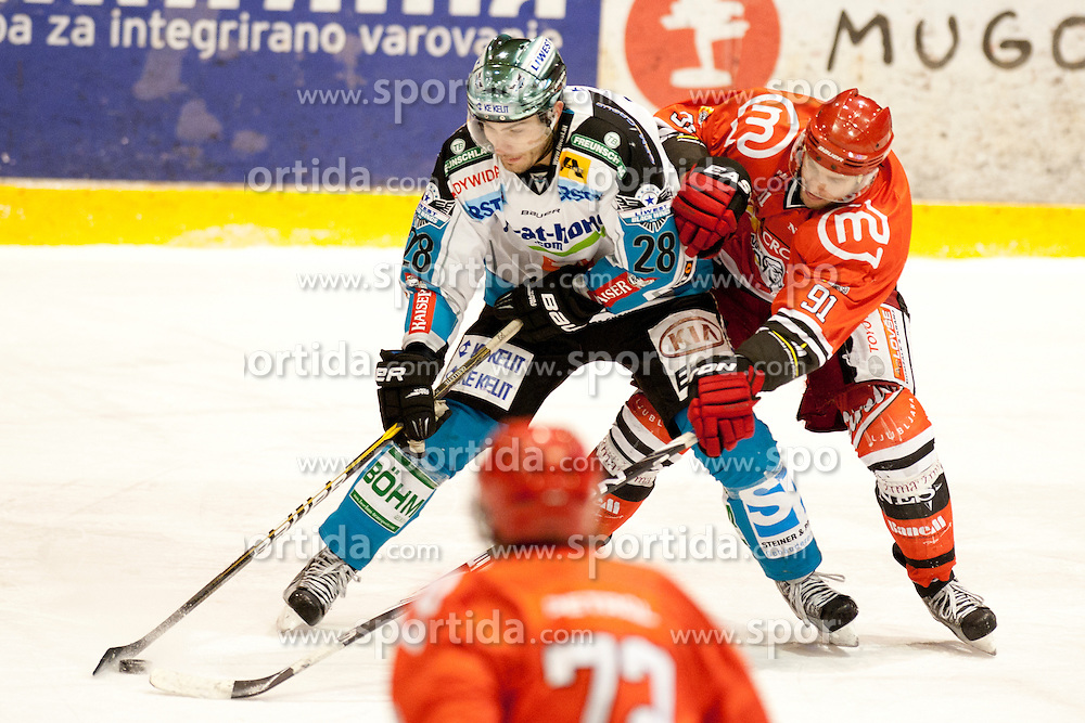 Ouellette Mike of EHC Linz and Hafner Tomi of HK Jesenice during ice-hockey match between HK Acroni Jesenice and EHC Liwest Black Wings Linz in 43rd Round of EBEL league, on Januar 17, 2012 at Dvorana Podmezaklja, Jesenice, Slovenia. (Photo By Urban Urbanc / Sportida)