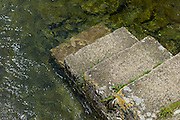 Ancient Cotswold stone steps into the River Leach at Eastleach Turville in the Cotswolds, Gloucestershire, UK
