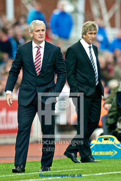 Picture by Ian Wadkins/Focus Images Ltd +44 7877 568959<br /> 14/09/2013<br /> Stoke City manager Mark Hughes  and Manchester City manager Manuel Pellegrini  during the Barclays Premier League match at the Britannia Stadium, Stoke-on-Trent.