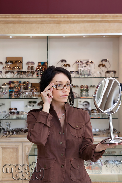 Beautiful mid adult female customer trying on glasses while looking into mirror
