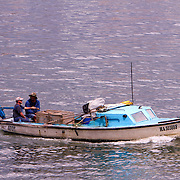 The small fishing boat motor into port on the River Almendares. Fishing is not only a favorite pastime for Cubans but it is also an income source.    Photography by Jose More